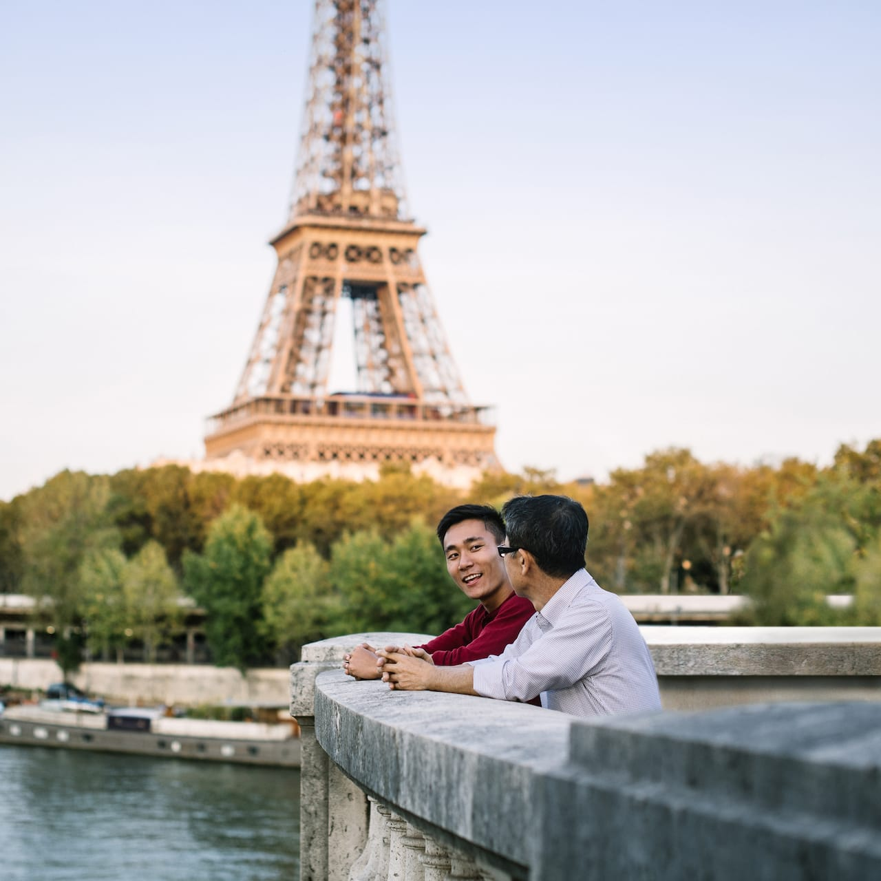 Two men stand with their arms resting on a cement railing overlooking the Seine River with the Eiffel Tower in the background
