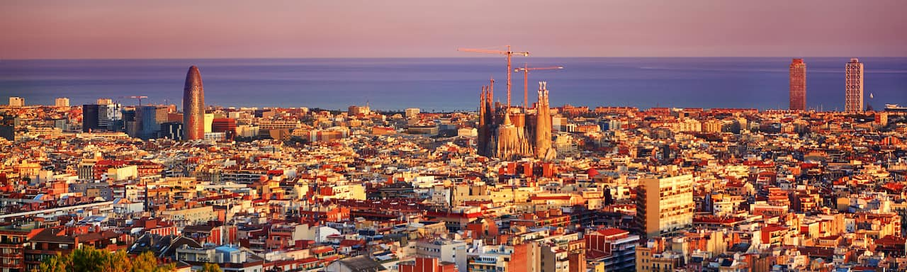 A view of the city of Barcelona with the Sagrada Famíla in the center and the Balearic Sea in the distance