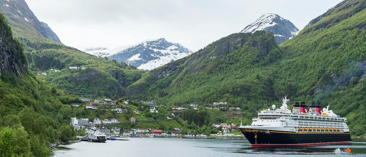 The Disney Magic cruise ship sails the waters between several lush mountains