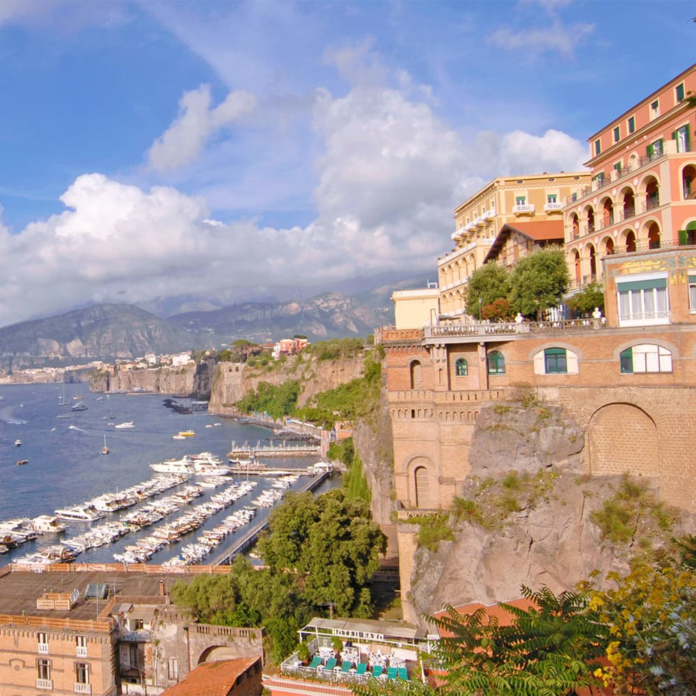 Buildings with arched balconies along the coast where boats line docks