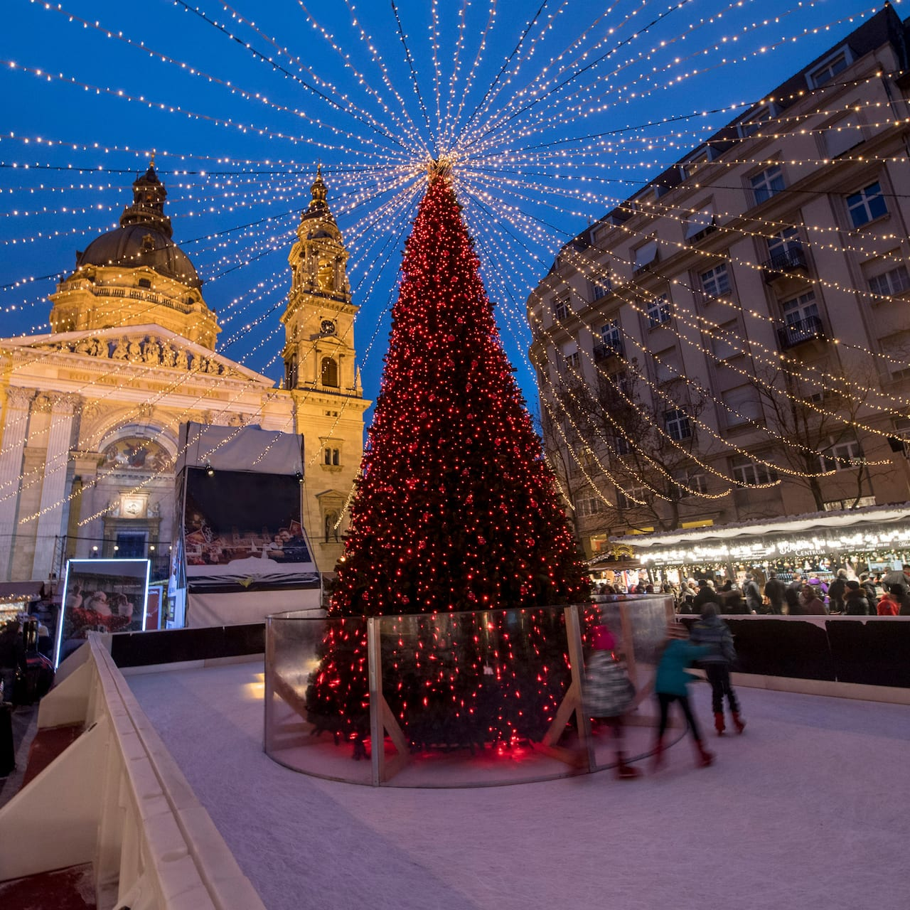 Kids ice skate around a Christmas tree lit up at night in front of St. Stephen's Church in Budapest, Hungary