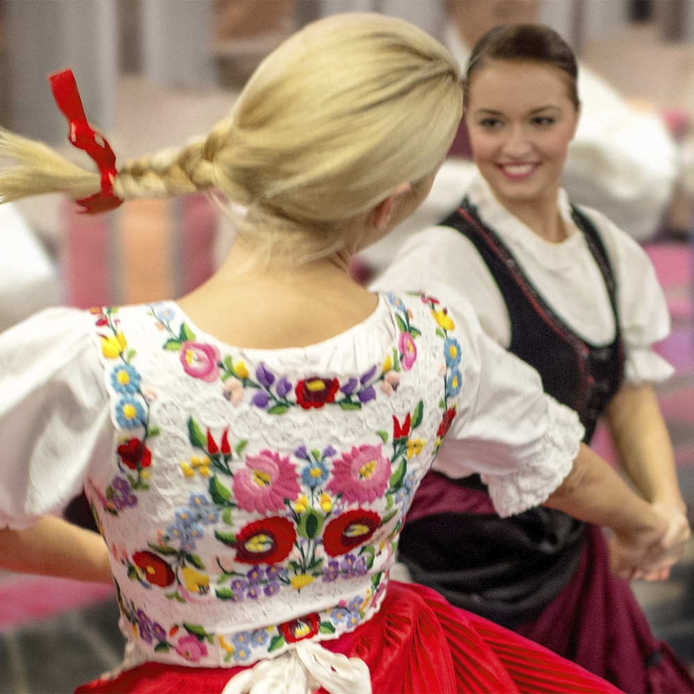 2 German women and a man dance a folkdance wearing traditional embroidered costumes