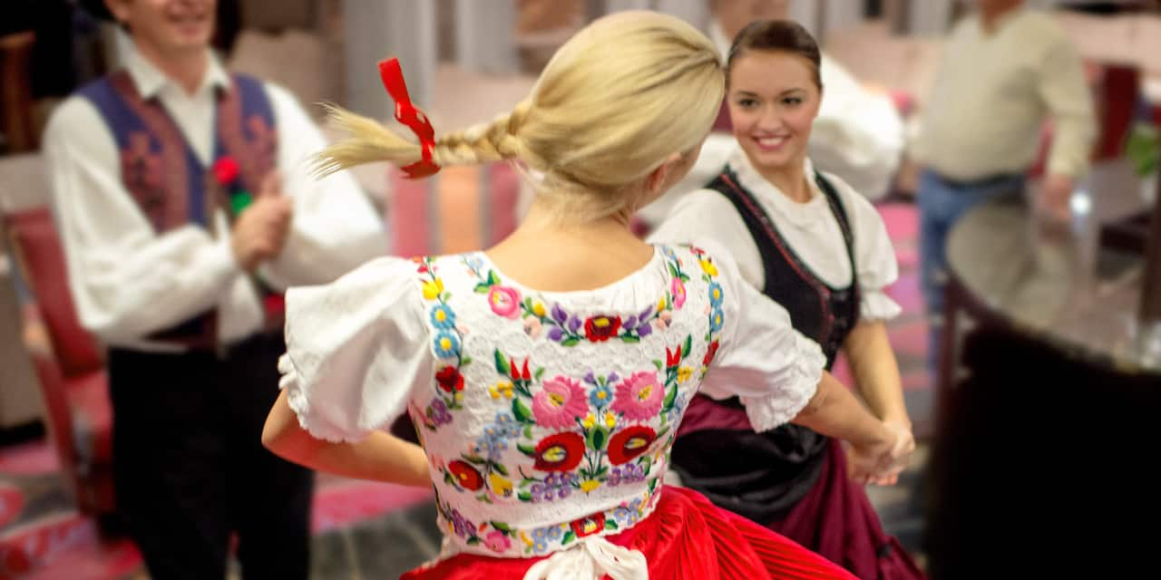 2 women wearing traditional costumes dance as a costumed male dancer claps