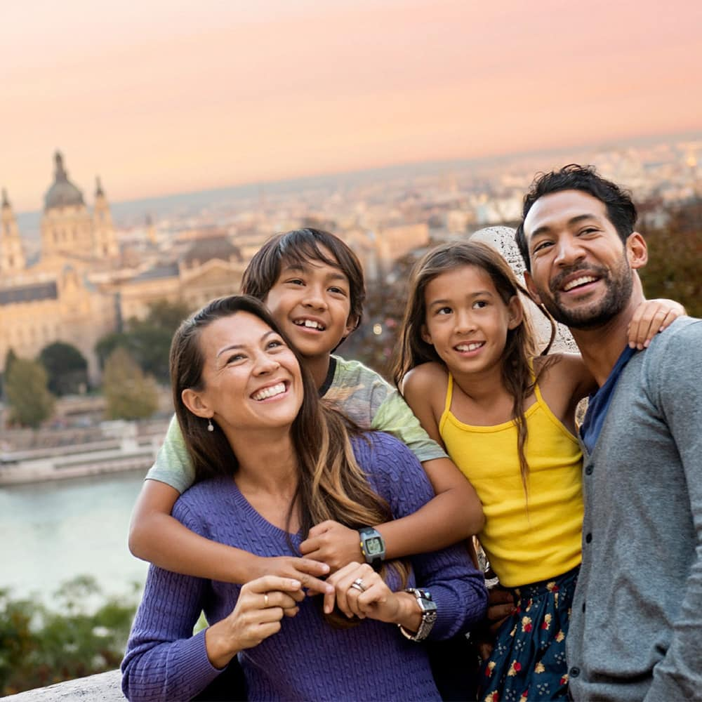 A family of 4 poses for a picture with the Danube River and Budapest skyline as a backdrop