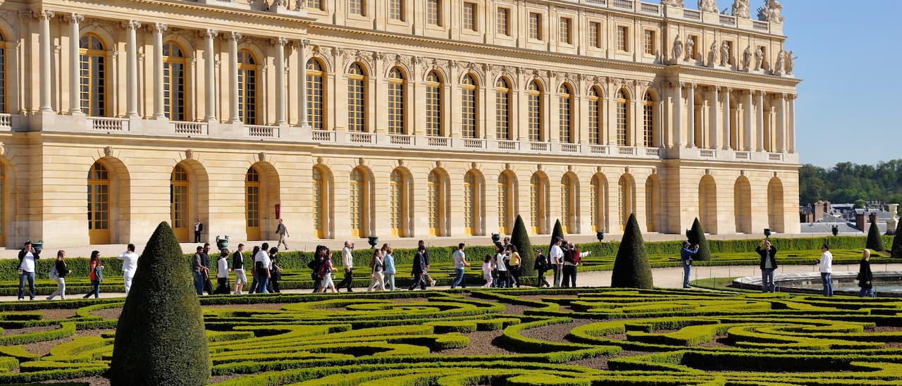 Tourists walk around the manicured gardens of the Château de Versailles
