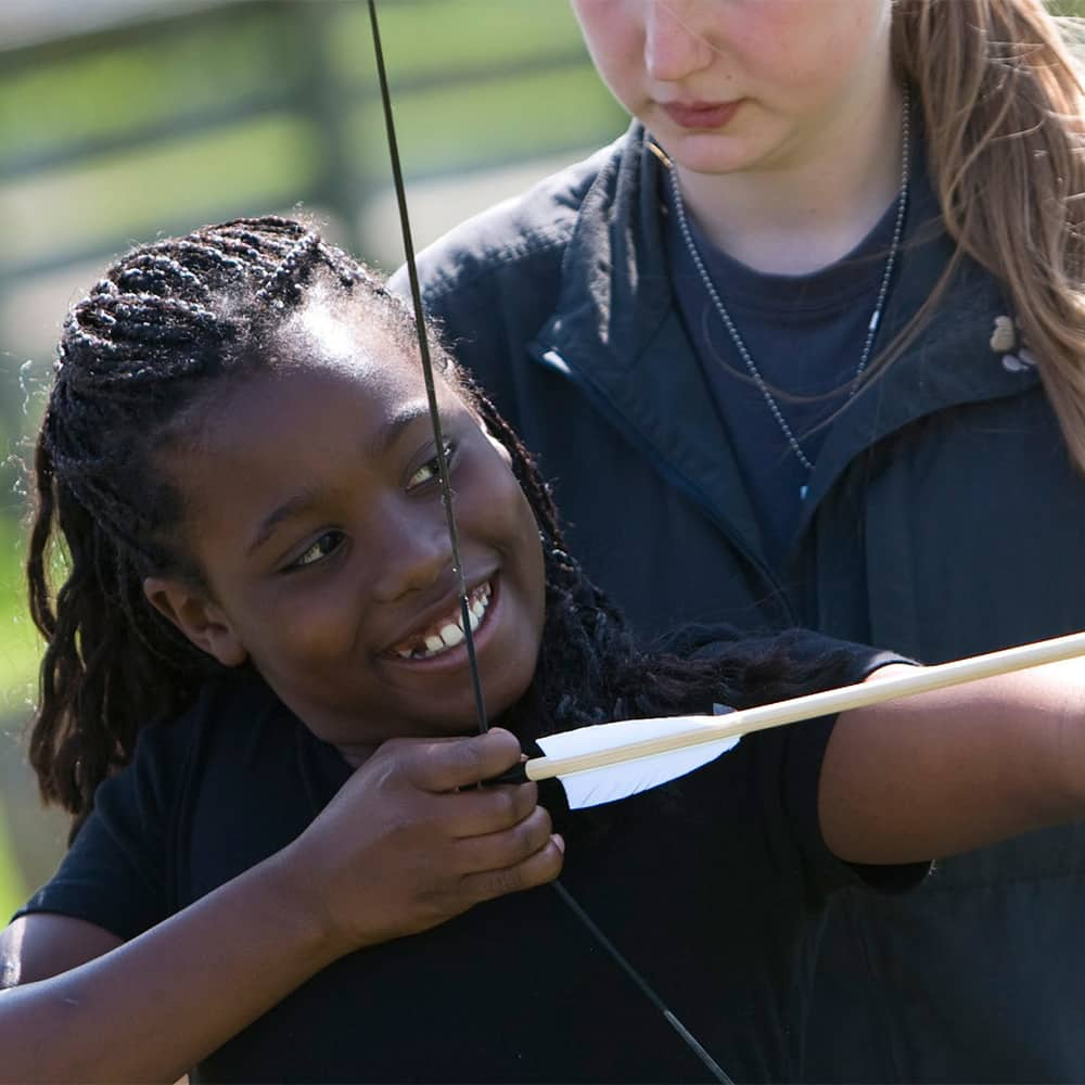 A girl holds a bow and arrow and aims