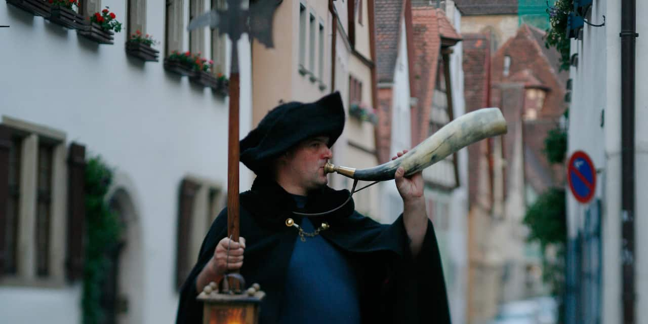 A costumed Night Watchman blows a horn