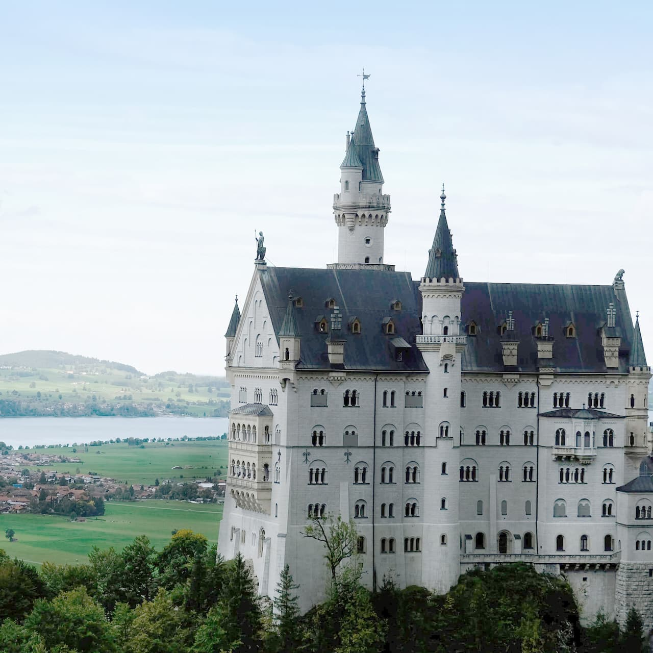 Neuschwanstein Castle stands on a hilltop above a town in the valley below on the banks of a river