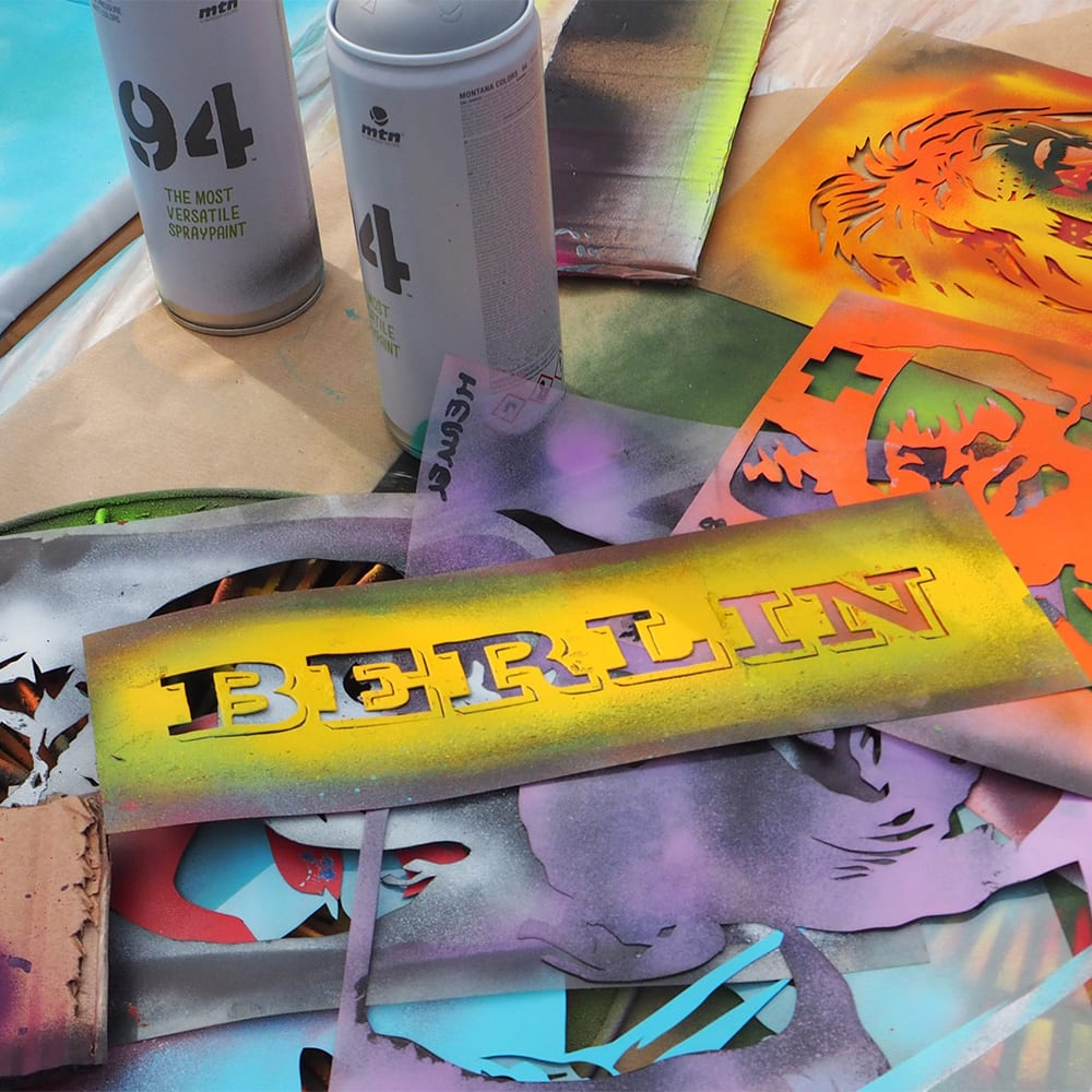 "A pile of graffiti stencils, including one that reads ""BERLIN,"" is next to 2 cans of spray paint"