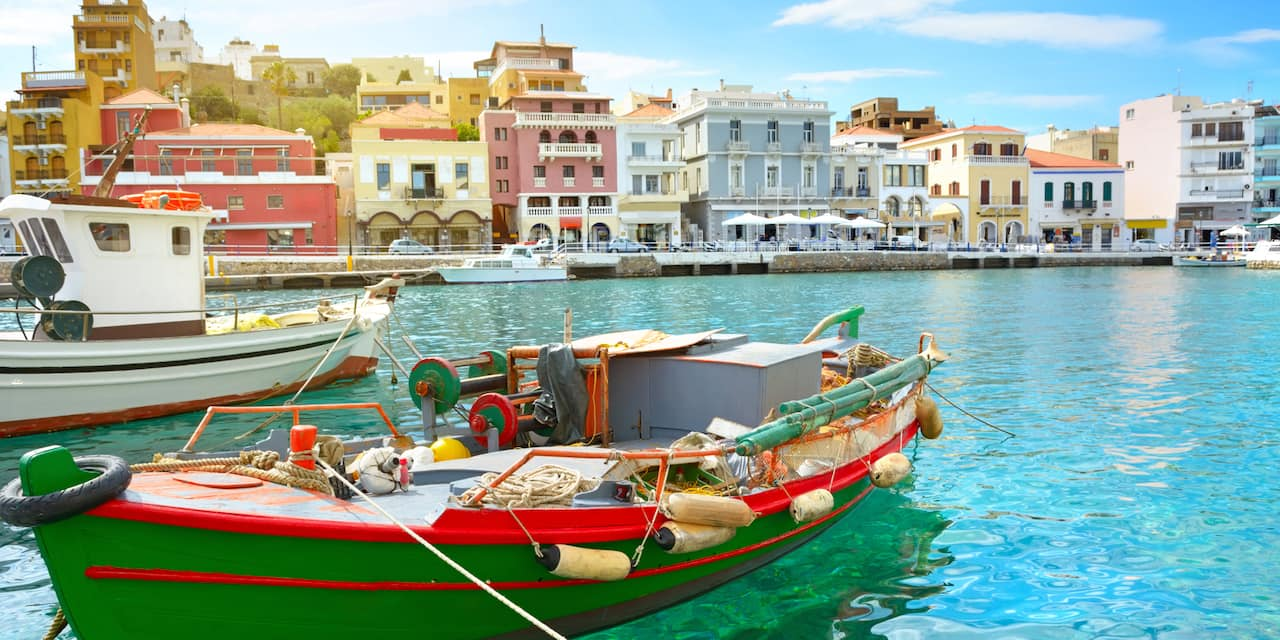 Two boats anchored in a harbor near a street lined with colorful houses in Crete