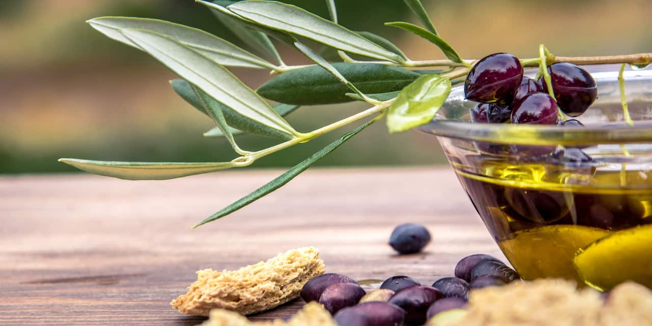 An olive branch rests on a glass bowl of olive oil