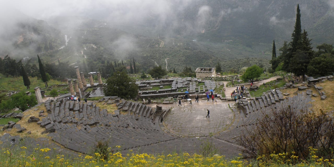 Tourists explore the Theatre of Delphi on a misty day