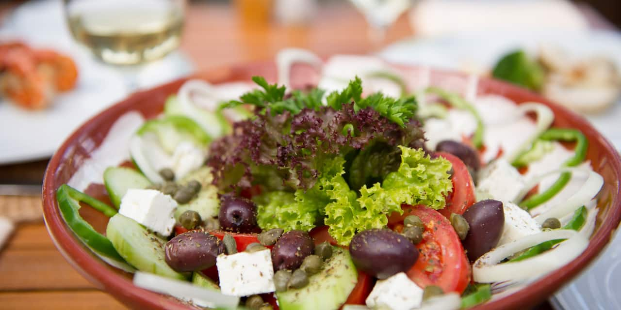 A Greek salad of onions, olives, tomato, lettuce and feta cheese is artistically arranged in a bowl