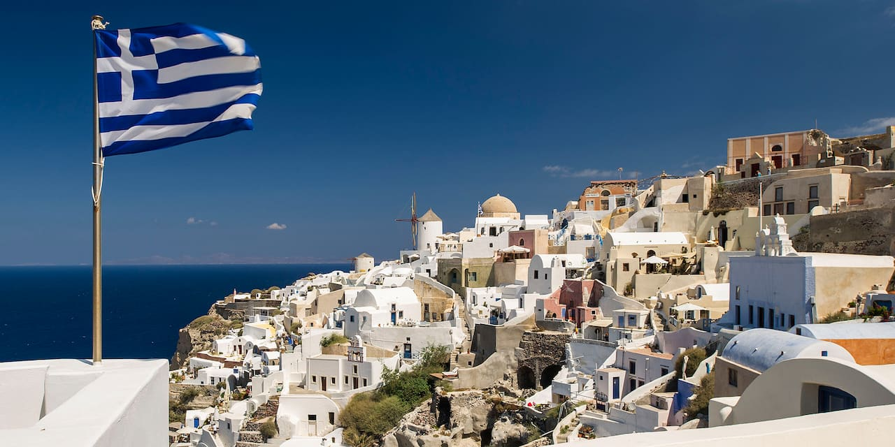 The Greek flag waves from a balcony with the city of Crete and the Aegean Sea in the background