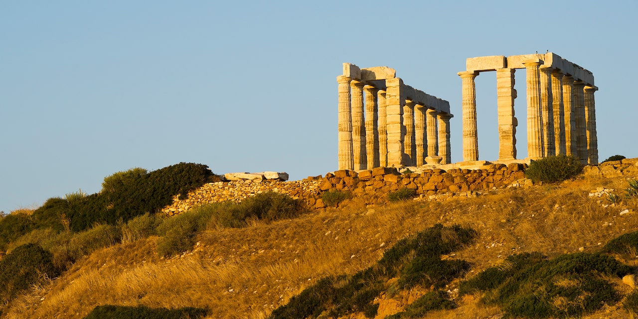 Two rows of upright columns stand among the ruins of the Temple of Poseidon atop a hill beneath a clear sky