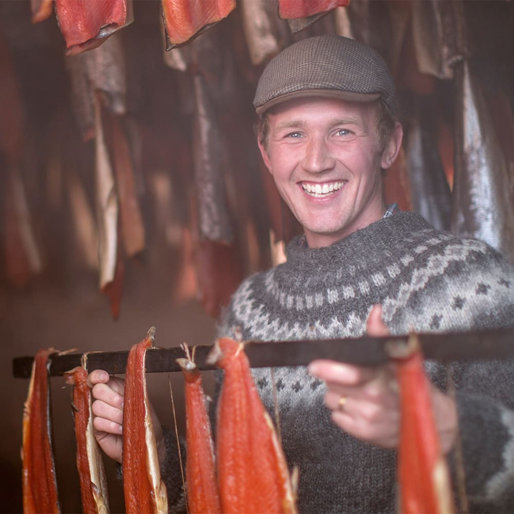 A smiling young man in a cap and sweater holds a rack of smoked food
