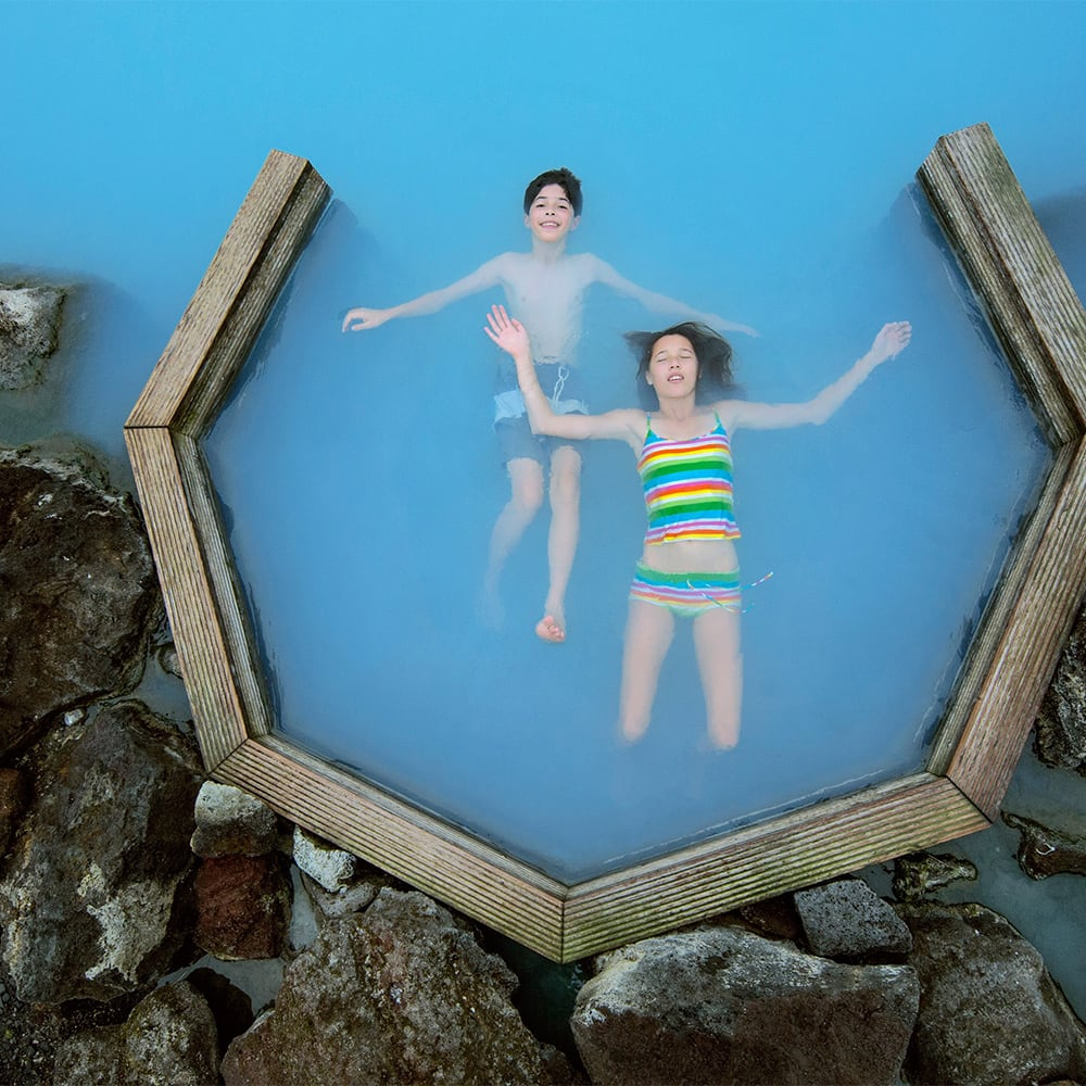2 kids in bathing suits float on their backs in one of the Myvatn nature baths