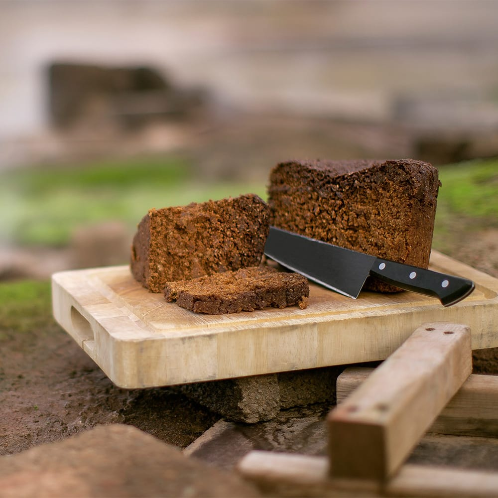 A knife rests between slices of Icelandic black bread that sits on a wood board