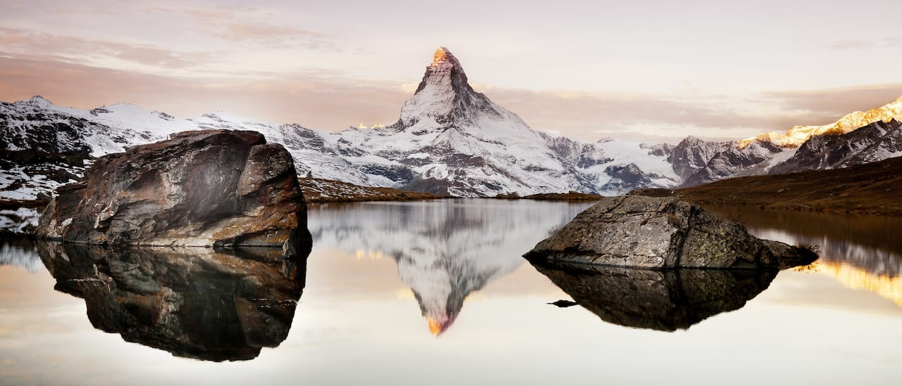 The famed, snow dusted Matterhorn and a rock studded lake