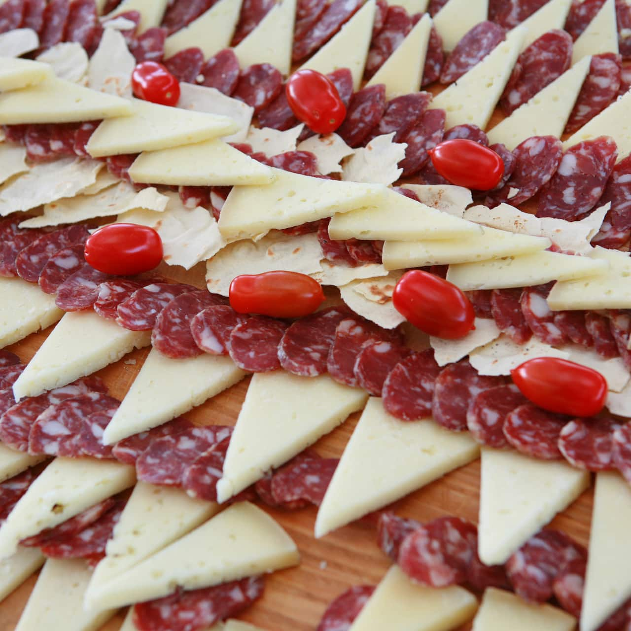 A display of meats, tomatoes and triangle-shaped cheese