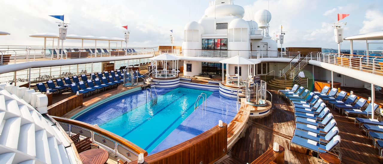 The upper deck pool area, with rows of deck chairs, of the Disney Magic cruise ship