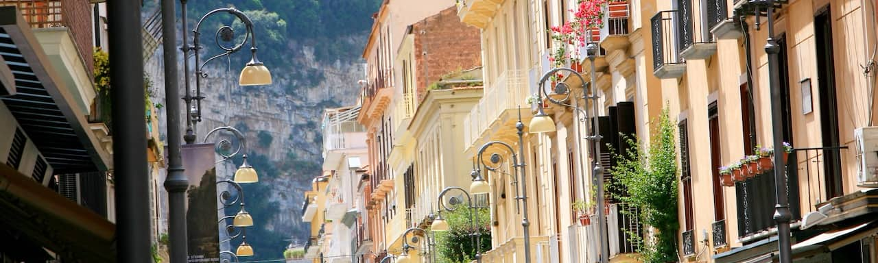 A row of buildings along a street lamp-lined avenue in Salerno, Italy lead to a verdant mountainside