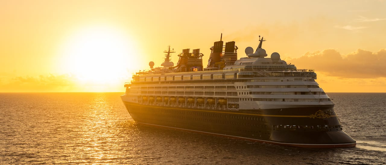 The Disney Magic cruise ship sails towards the sunset