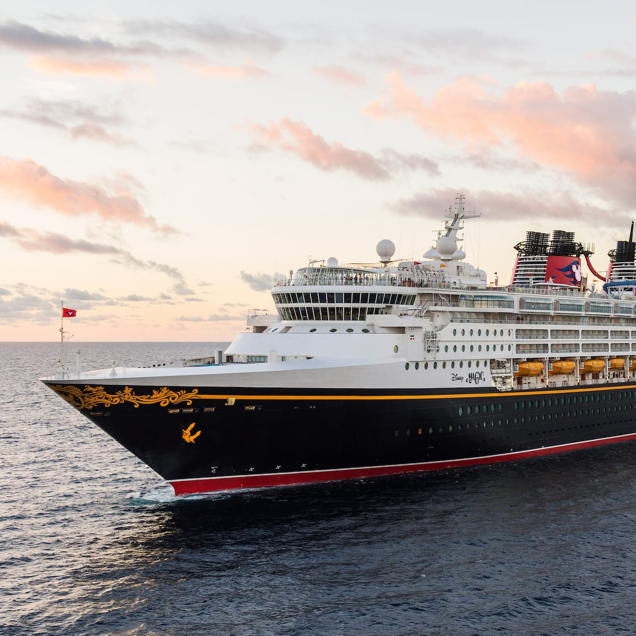 The Disney Magic cruise ship sails the sea beneath a cloudy sky
