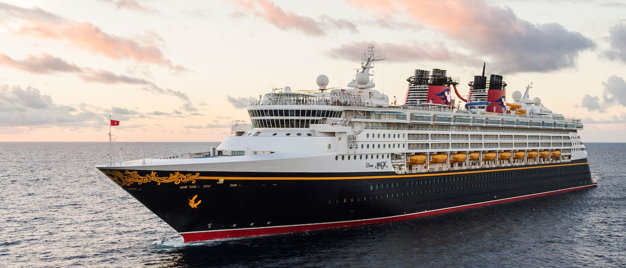 The Disney Magic cruise ship sails the sea beneath a cloudy sky