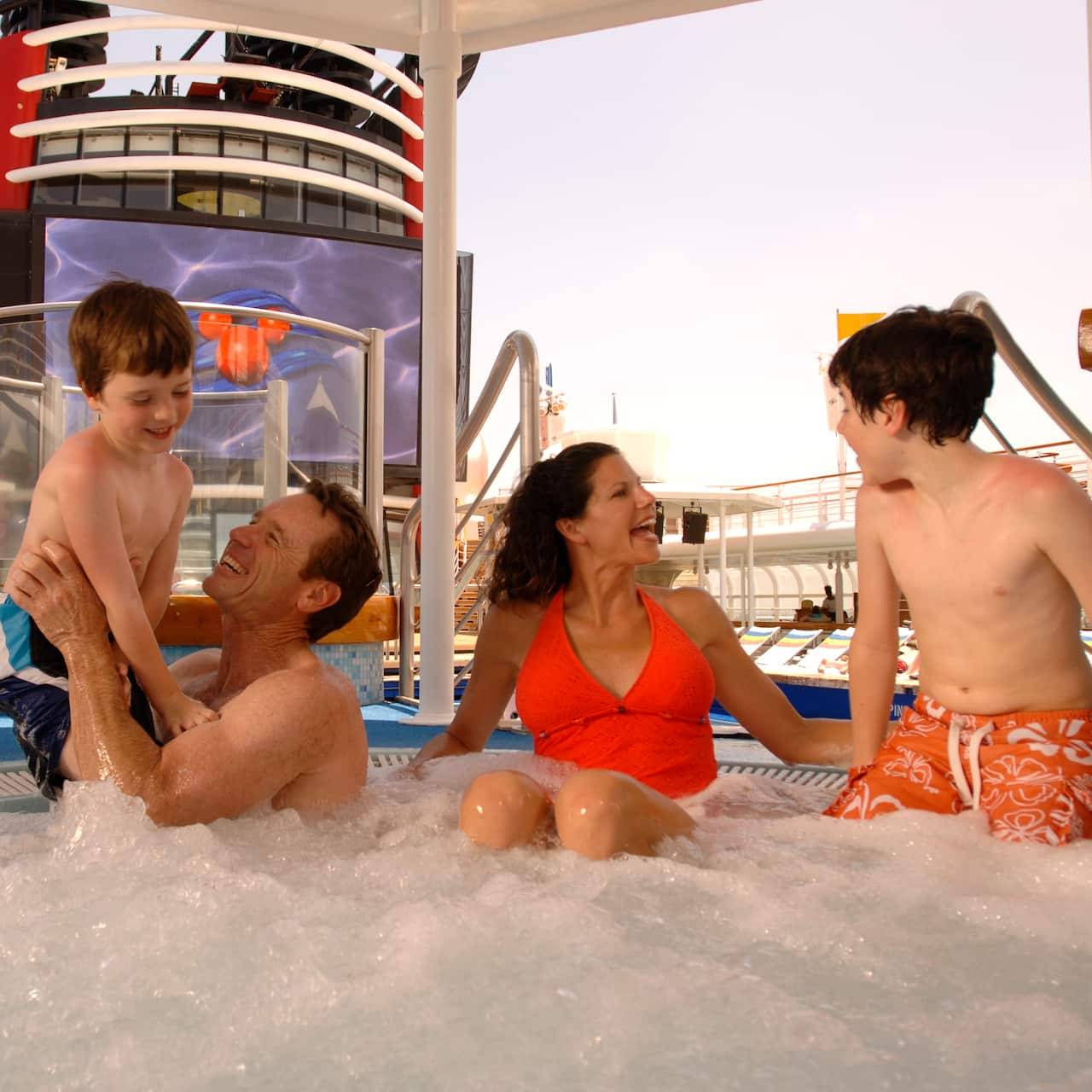 A family of 4 sit in one of the pools on board the Disney Cruise Line cruise ship, Disney Magic