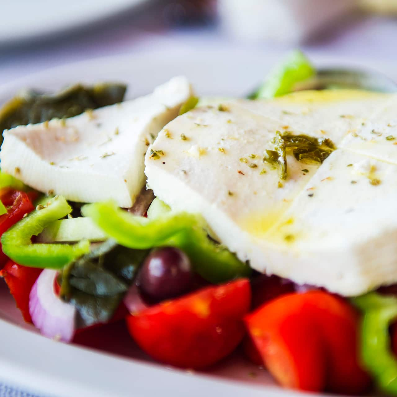 A plate with several pieces of mozzarella cheese, green peppers, tomatoes and Greek olives