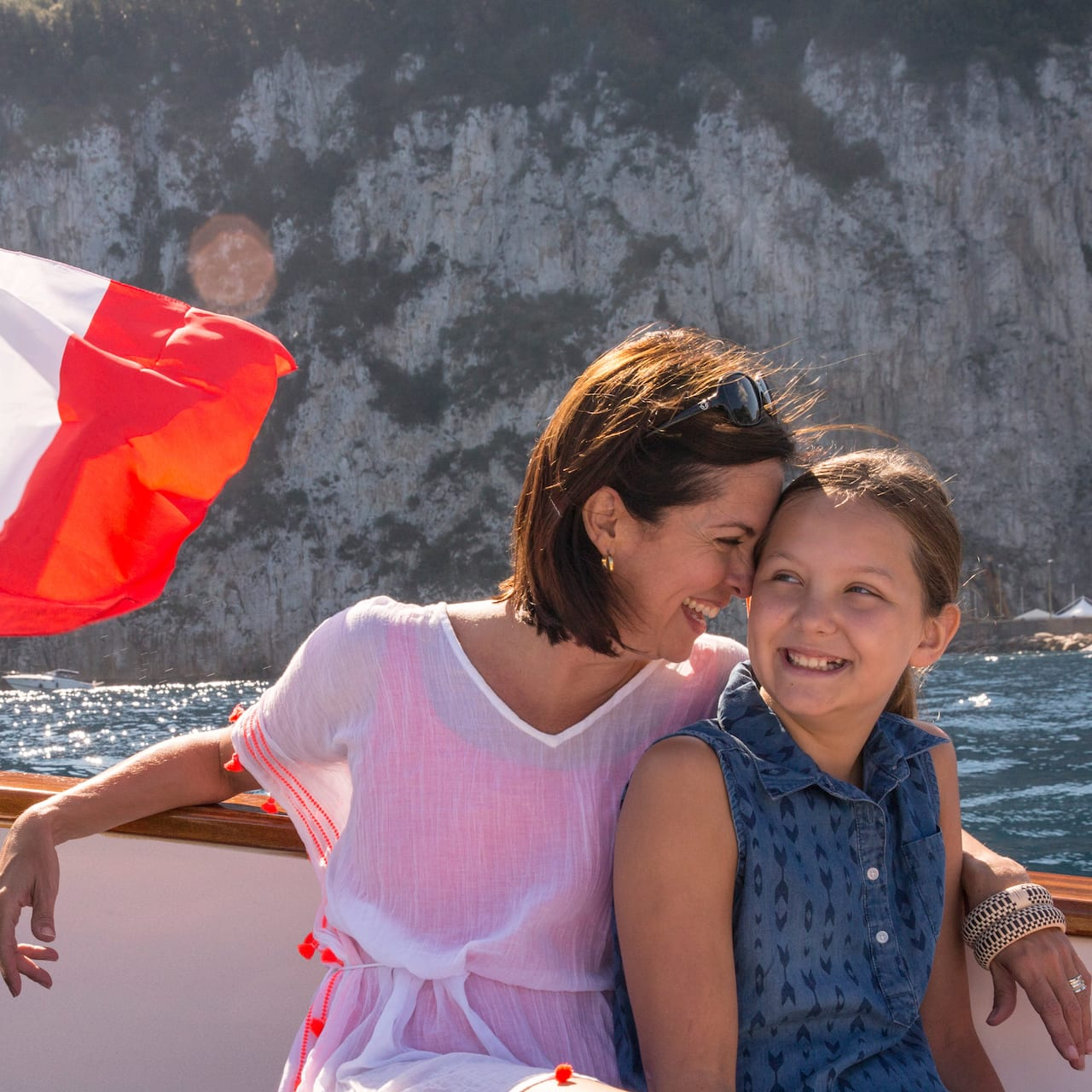 A woman presses her head against her young daughter's forehead as they ride a boat that flies the Italian flag