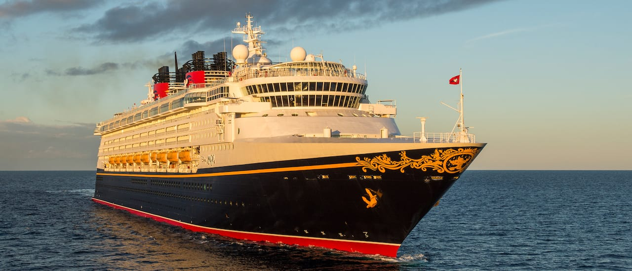 The Disney Magic cruise ship sails across the sea with a cloudy sky
