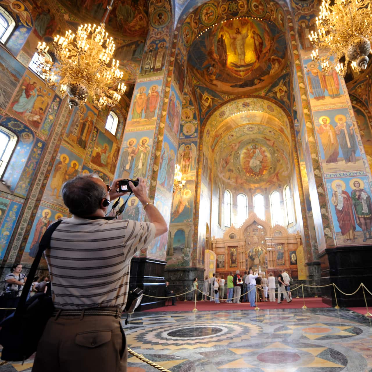 A man takes a photo of the murals and ornate interior décor of the Church of the Savior on Spilled Blood in St. Petersburg, Russia
