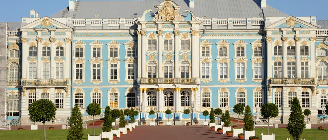The tree-lined driveway leding to the grand front façade of the Winter Palace in St. Petersburg, Russia