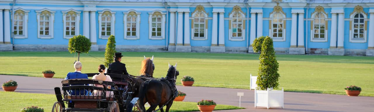 A buggy driver takes a couple on a horse and buggy ride at the grounds of a palace