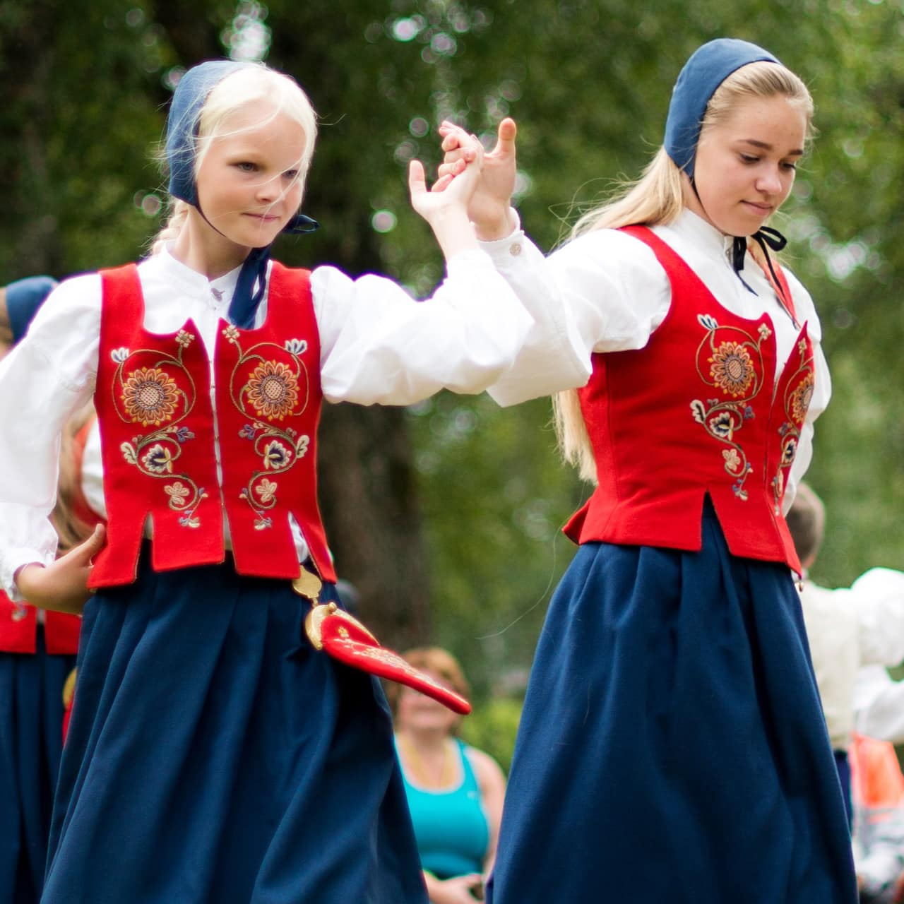 4 Norwegian girls dressed in traditional costumes folk dance
