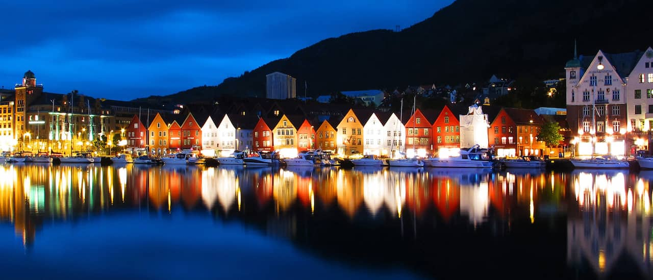 At night, lit storybook houses reflected in a harbor containing docked boats