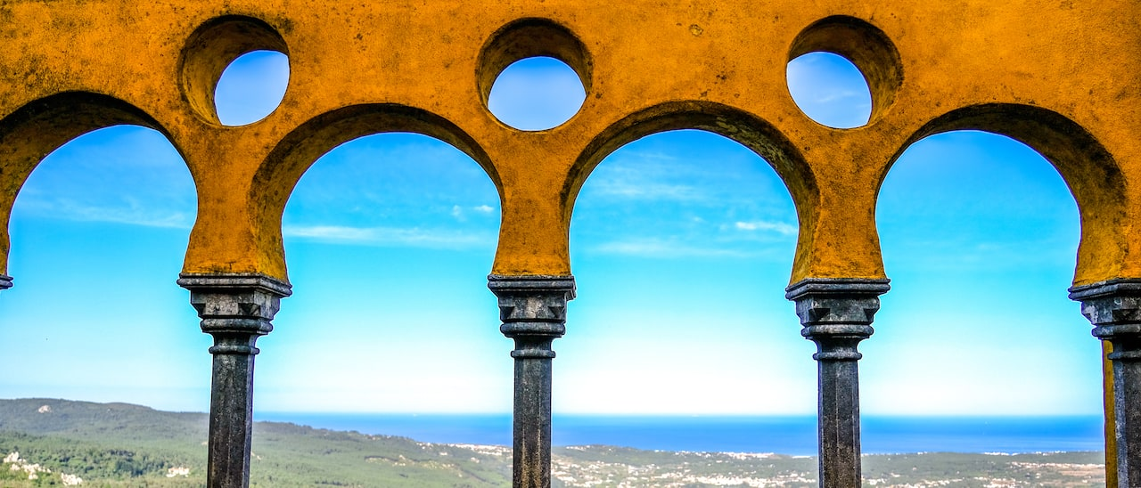 An archway with circular patterns with a view of the ocean in the distance