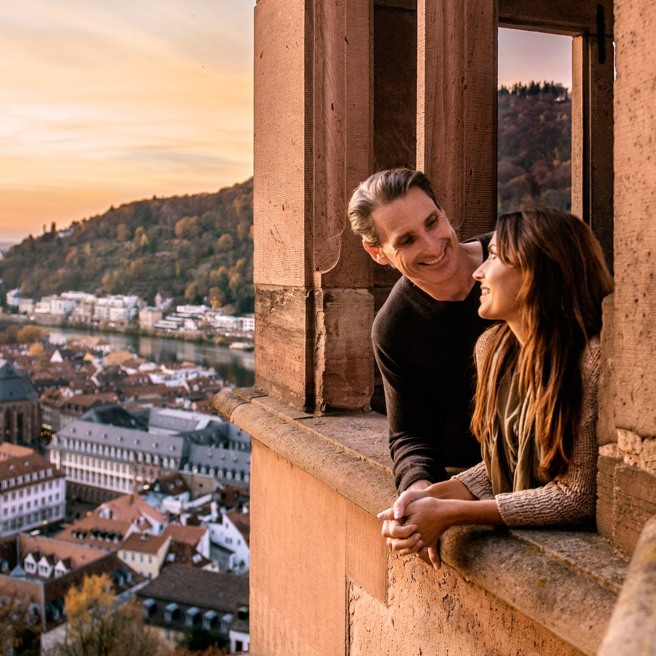 A man and woman share a romantic moment while looking out of a window at Heidelberg Castle with the city of Mannheim in the distance