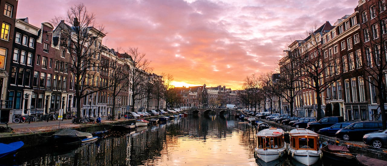 A canal with parked boats runs through 2 building-lined streets in Amsterdam