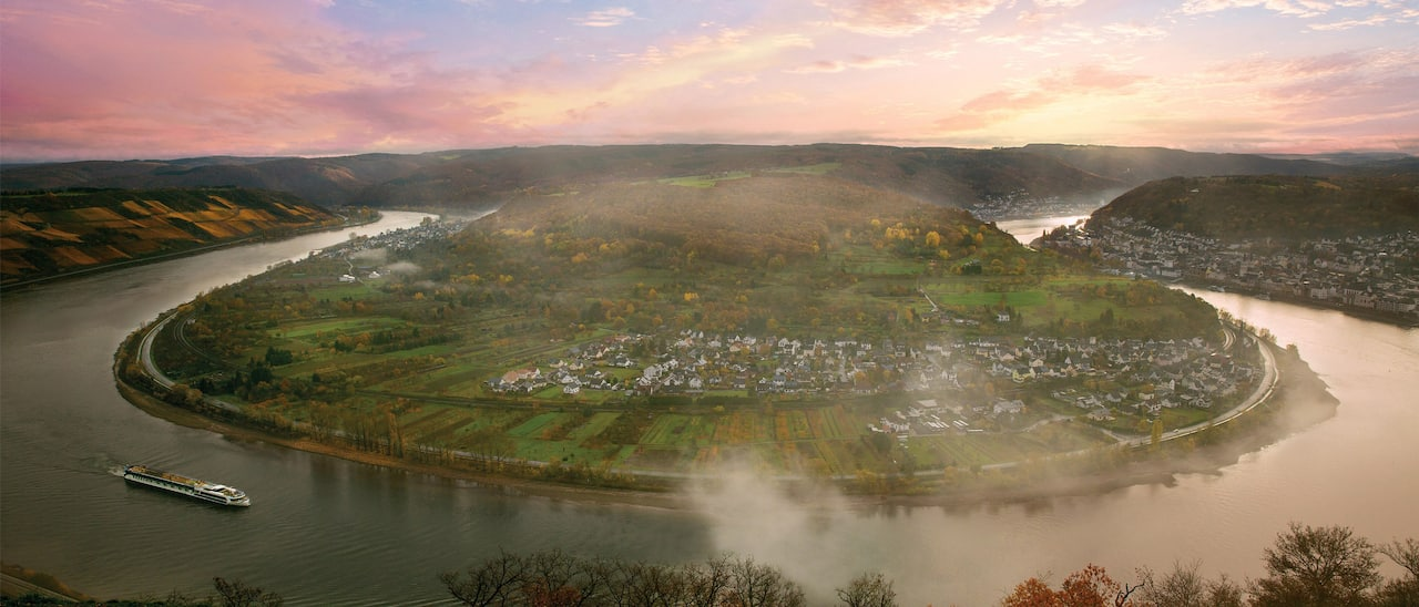 A horseshoe bend along the Rhine River with a town and lush landscapes surrounding an inner island