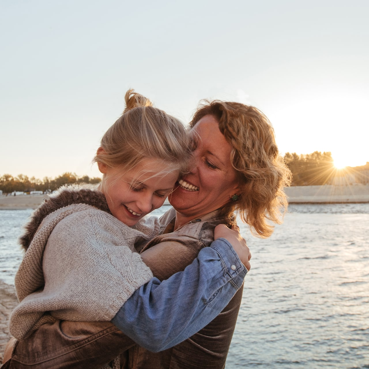 A mom and daughter hug on a path along the Rhône River with a river cruise ship in the background