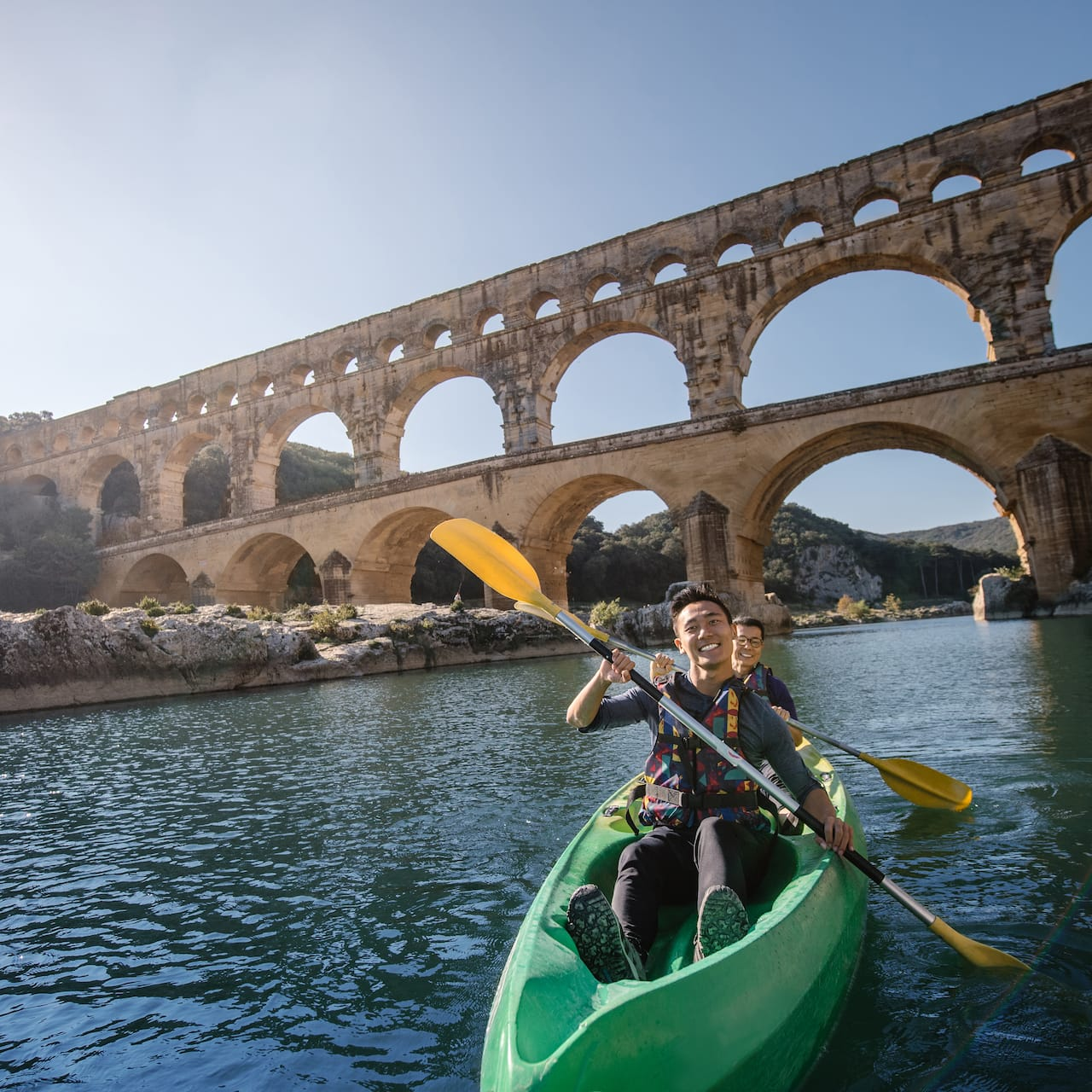 A pair of Adventurers kayak in the river near the Pont du Gard aqueduct