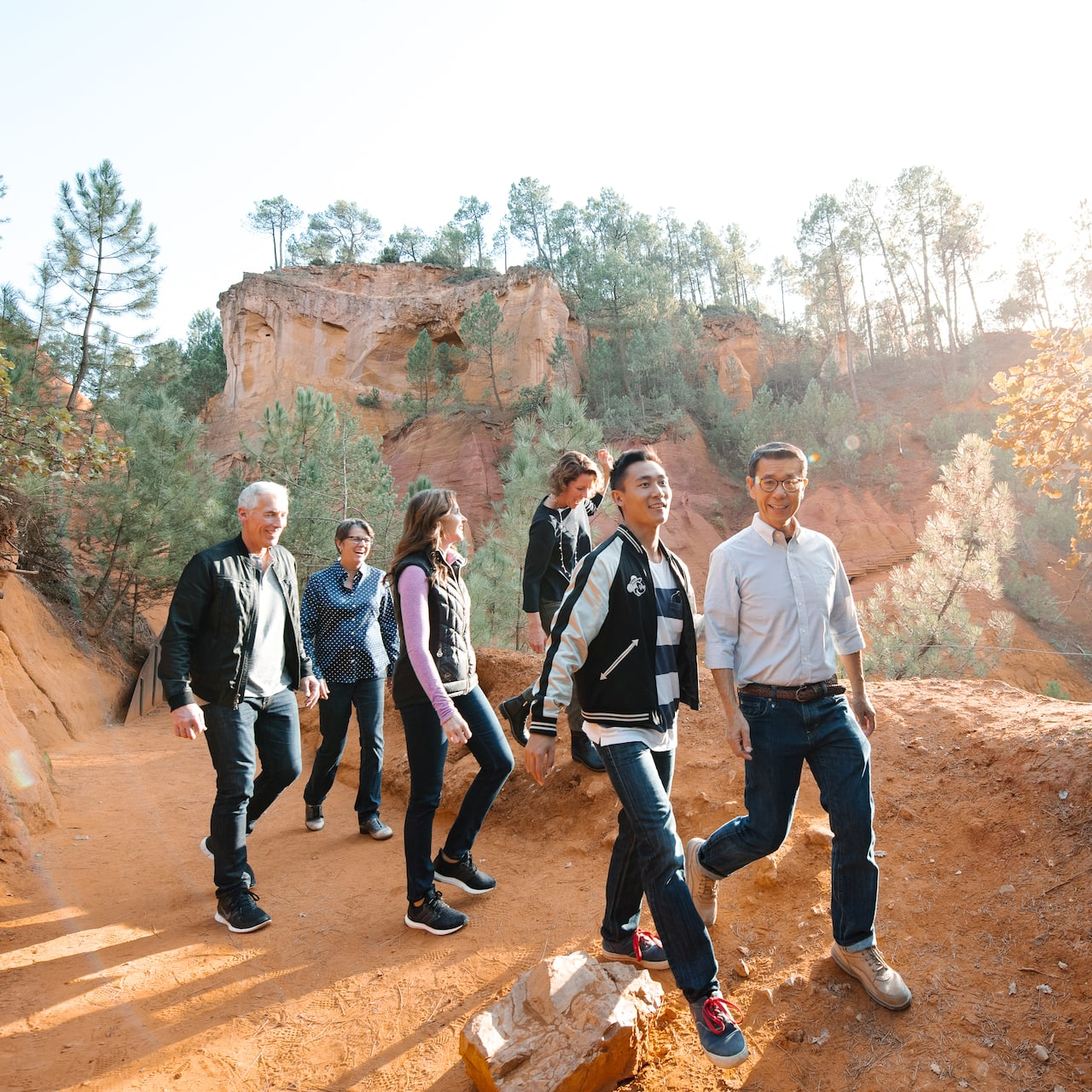 A group of 5 people walk along the Ochre Trail in Luberon, France