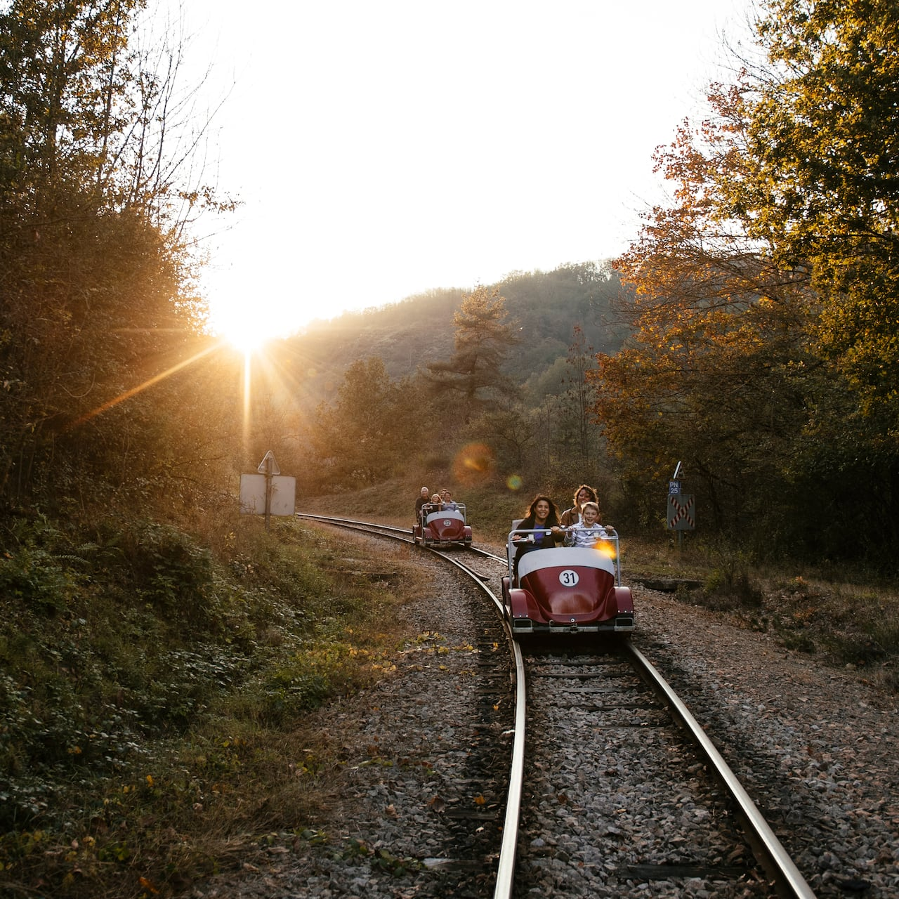 Two rail cars ride along the Vavarais Railway tracks at sunset