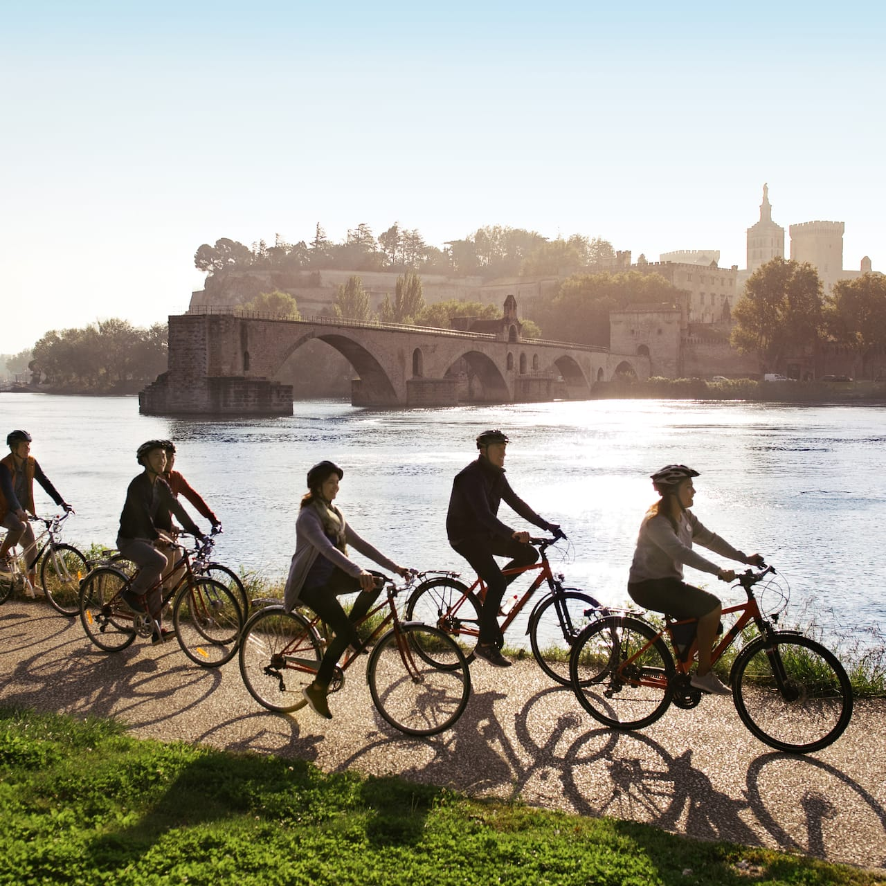 A group of 6 Adventurers follow an Adventure Guide on a bike ride down a bike path along the Rhône River