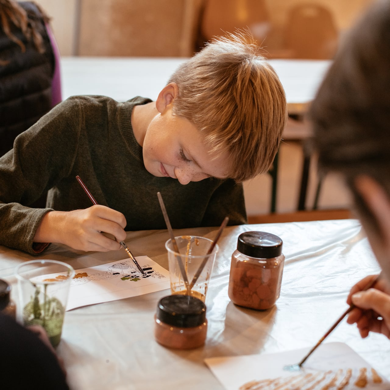 A boy paints while seated at a table with art supplies