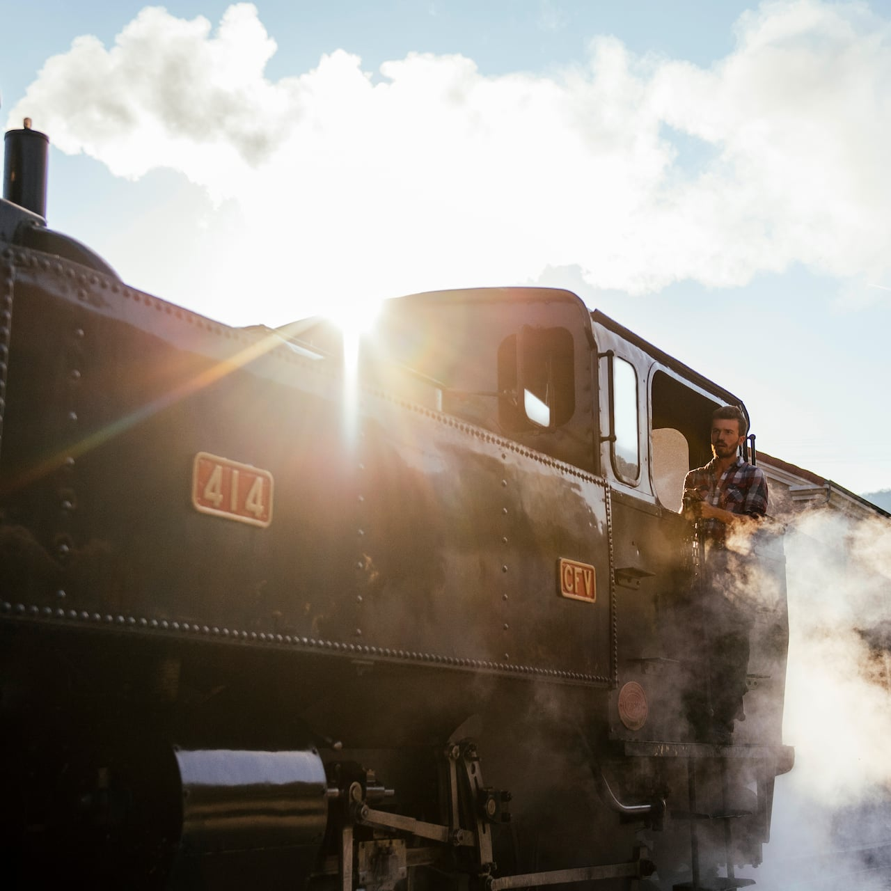 A conductor drives a steam engine train