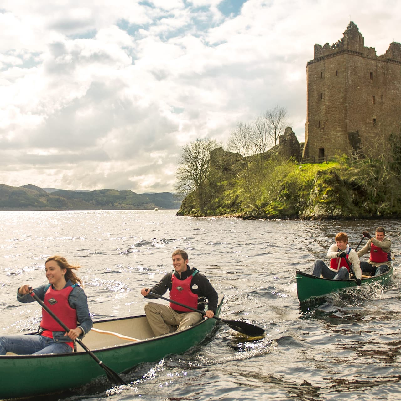 4 Adventurers paddle 2 canoes past Urquhart Castle on Loch Ness